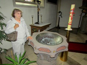 Gloria Temple stands at a baptismal font where her ancestors were baptized in Grosseneder, Germany