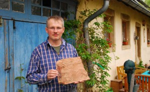 Roland Geiger holds a tile nearly 2,000 years old found in the parking lot of his home in St. Wendel, Germany.